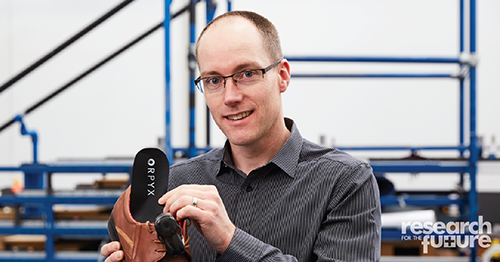 Neil Reeves inserting an insole into a shoe