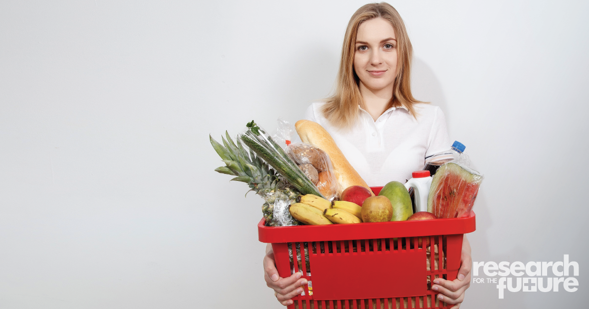 Young woman holding a shopping basket of food
